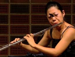 Dando un concierto de flauta con una mariposa en la cara